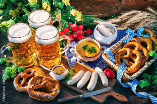 Bavarian sausages with pretzels, sweet mustard and beer mugs on rustic wooden ta Fototapete