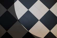 Top View Of Black And White Square Checked Table Pattern On The Floor, With Light From Spotlight At The Corner