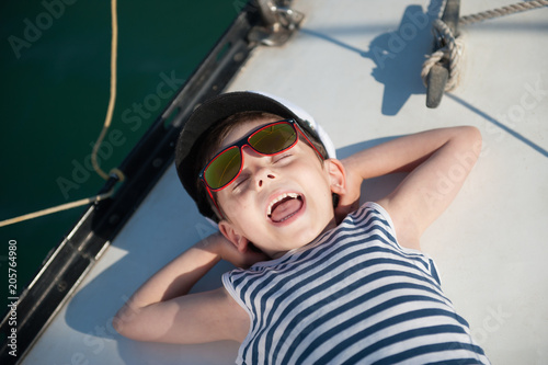 funny laughing small kid in captain hat lying on board luxury yacht laughing