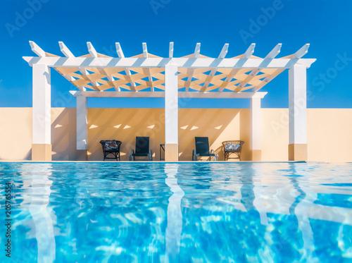 White poolside pergola, gazebo taken from the swimming pool Fototapeta