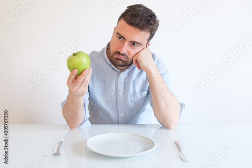 Sad and frustrated man on diet having only fruit for meal Wallpaper Mural