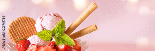 Ice cream cup with strawberries and waffle