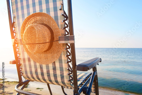 Beach accessories, woman's hat affixed to deck chair back Wallpaper Mural