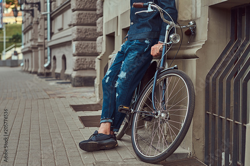 Fototapety, obrazy: Cropped image of a fashionable man in stylish clothes leaning against a wall with city bicycle on the street.