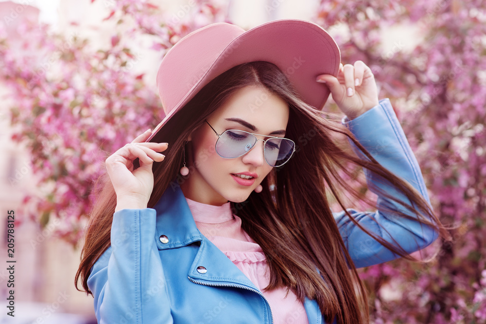 Fototapety, obrazy: Young beautiful fashionable girl wearing stylish blue color aviator sunglasses, pink suede hat, earrings, biker jacket. Model posing in street with flowering trees. Spring fashion concept.