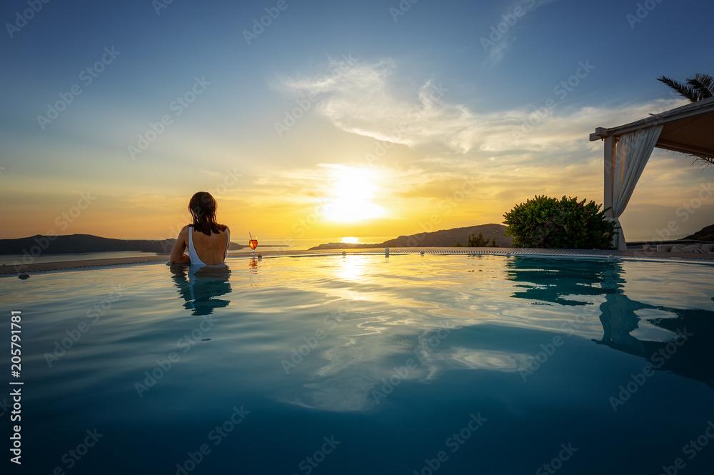 Fototapeta Woman relaxing at the edge of infinity swimming pool at sunset