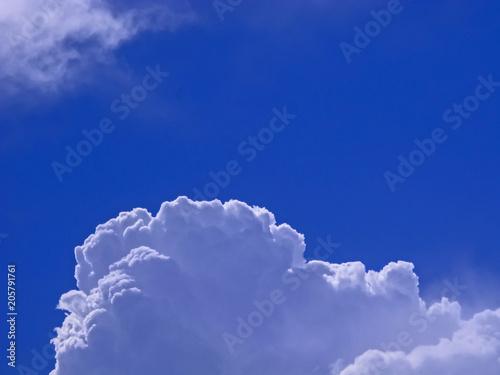 Fotografiet  Biała, kłębiasta chmura na błękitnym niebie.