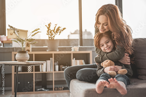 Full length portrait of affectionate mom cuddling her kid with delight. Small girl is holding her teddy bear with her legs stretched. Copy space in left side