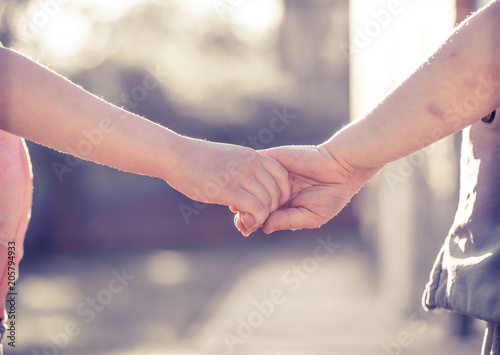 Little Girl And Boy Hold Hands Close Up Against The Backdrop Of A