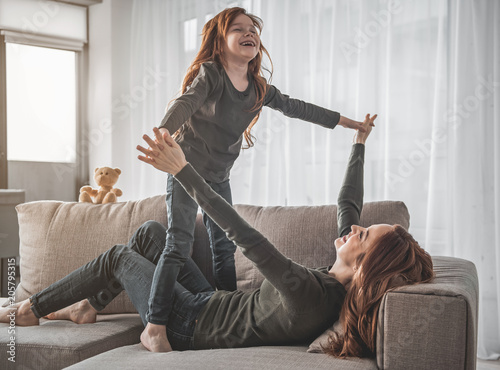 Fotobehang Wintersporten I believe I can fly. Full length portrait of small smiling girl and her amused mother are lying on sofa with their fingers crossed while entertaining. Cheerful child pretending being bird