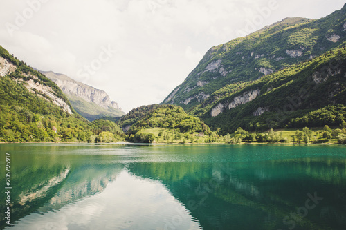 Lago di tenno with mountain and trees reflection in water Wallpaper Mural