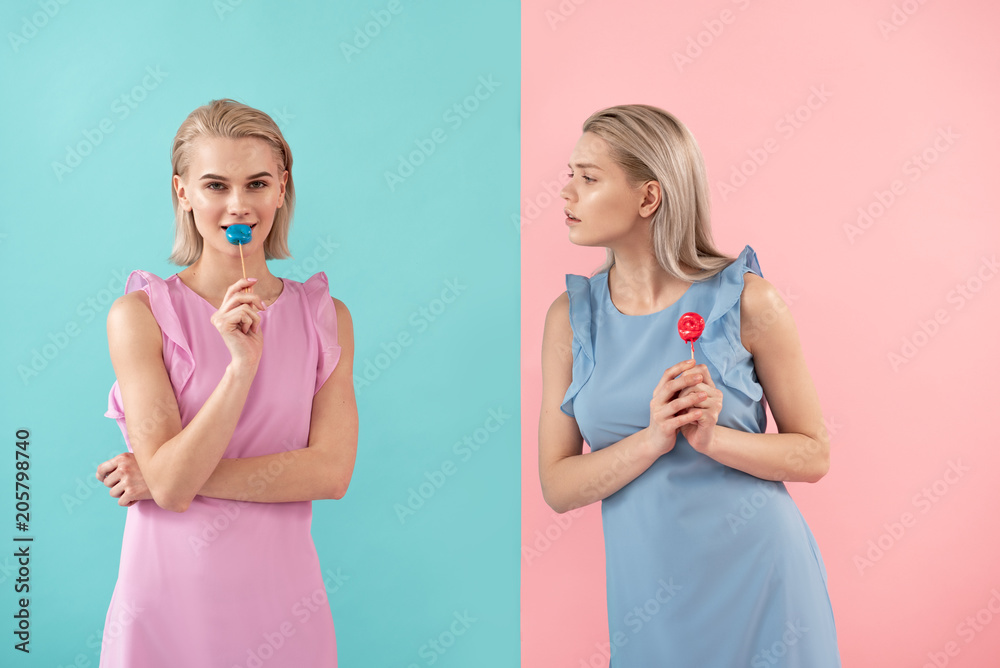 Fototapety, obrazy: Two girls holding sweets on stick. One looking at another with envy. Isolated on blue and pink background