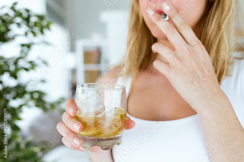 Keuken foto achterwand Bar Young woman drinking glass of whiskey and smoking at home.