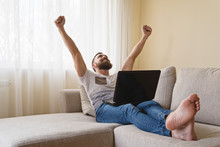 Happy Bearded Man Freelancer, Student Working At Computer At Home And Celebrating Victory With Raised Hands And Screaming