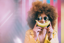 Surprised Mixed Race Woman In A Colorful Artwork Background Wall Playing With A Banana