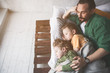 canvas print picture - Top view happy father embracing serene tired kids while resting in room