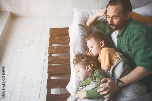 Fotografia  Top view happy father embracing serene tired kids while resting in room