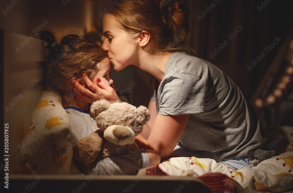 Fototapety, obrazy: mother puts her daughter to bed and kisses her in   evening