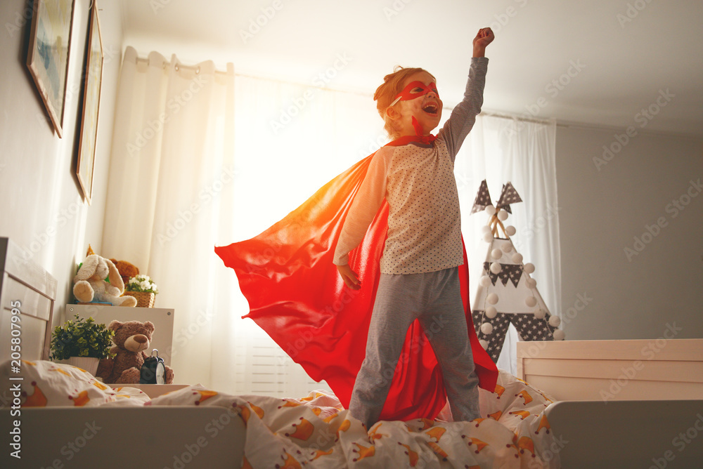 Fototapeta child girl in a super hero costume with mask and red cloak
