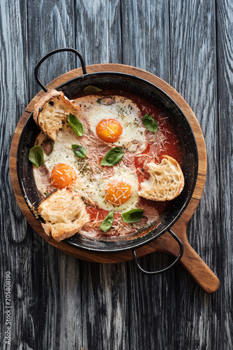 Fotobehang Wintersporten top view of delicious fried eggs with cheese, bread and sauce in pan on wooden cutting board
