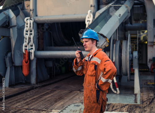 Fotografia  Marine Deck Officer or Chief mate on deck of marine vessel or ship , wearing PPE personal protective equipment - helmet, coverall