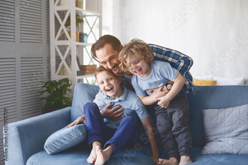 Fotografering Portrait of laughing dad hugging beaming kids having entertainment on sofa in living room
