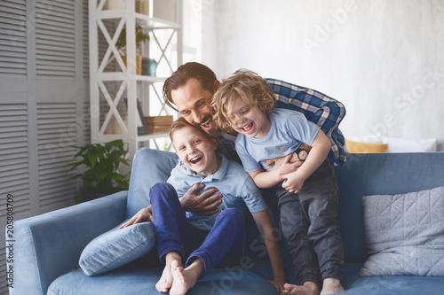 Fotografiet  Portrait of laughing dad hugging beaming kids having entertainment on sofa in living room