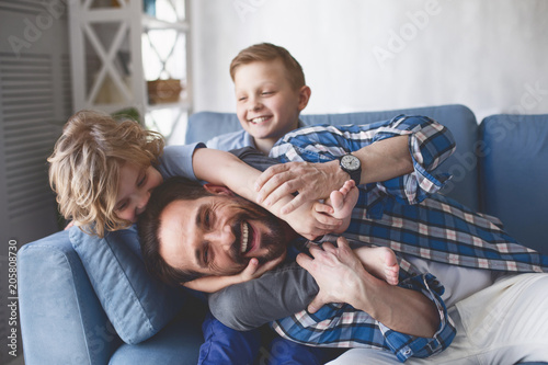 Portrait of smiling father and outgoing sons having fun on cozy couch in apartment. Happy family concept
