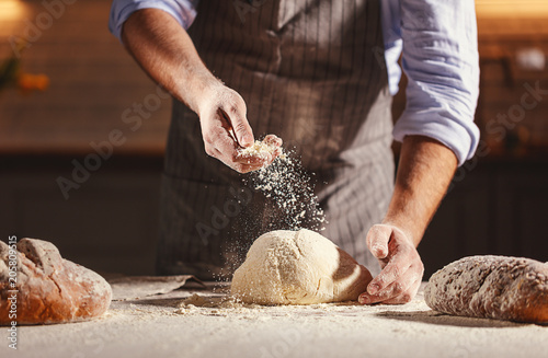 Fotobehang Bakkerij hands of baker's male knead dough