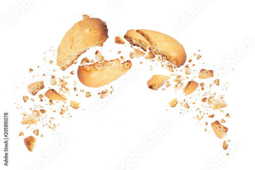 Photo  Biscuits broken into two halves with falling crumbs down, isolated on white back