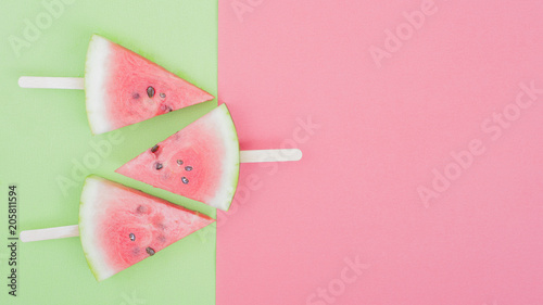 watermelon slice on green and pink background with stick
