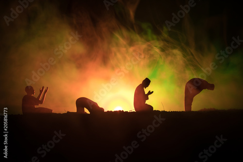 Silhouette of praying Muslim man on toned foggy background Canvas Print