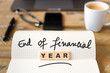 Closeup on notebook over wood table background, focus on wooden blocks with letters making End of Financial Year text