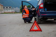 A broken car on the road, a red triangle of warning on the road, a driver in a red vest, worried, needs help, road assistance
