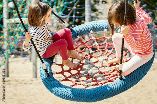 two little girls are swinging on a swing at the playground on a summer day