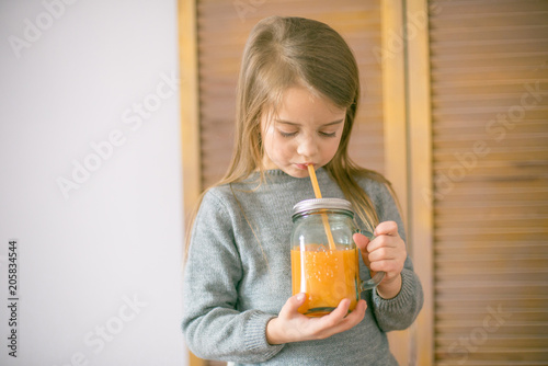 Fotobehang Sap Cute little girl with glass of orange juice at home, closeup
