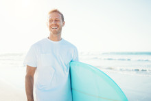 Smiling Guy Surfer Walking With Surfboard Near The Ocean