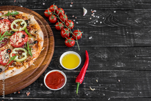 Spoed Foto op Canvas Pizzeria Vegetables, mushrooms and tomatoes pizza on a black wooden background. It can be used as a background
