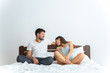 The man and a woman sitting on the bed on the white background