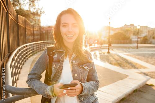 Fotografía  Happy woman outdoors using mobile phone