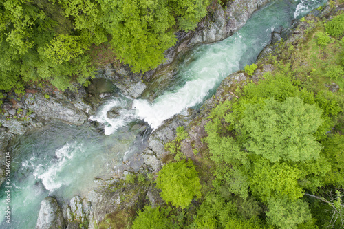 Aerial view of a mountain river flowing between rocks and forests in spring. River Sesia in Valsesia, Piedmont, Italy.