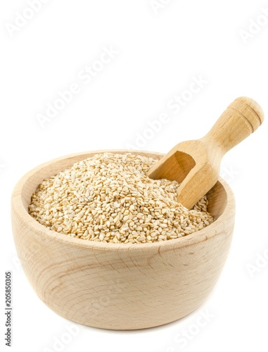 A wooden bowl of sesame seeds and a scoop on a white background with copy space