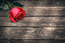 Red Rose Flower On Aged Wooden Table Background With Copy Space.