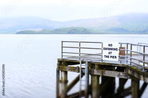 Fotografie, Obraz  No swimming at pier jetty deep water Loch Lomond Luss warning sign danger of dea