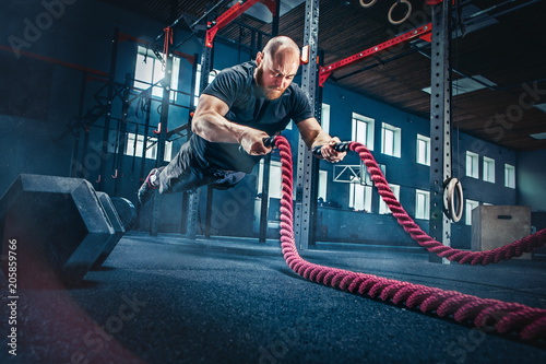 Tuinposter Fitness Men with battle rope battle ropes exercise in the fitness gym.
