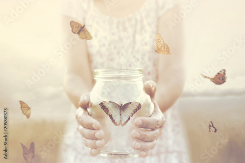 Fotografía  woman gives freedom to some butterflies enclosed in a glass vase