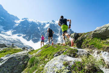 Fototapeta Trail runners running up a steep trail in the Alps in summer