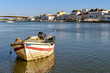Colorful boat on Gilao river and view of the city of Tavira, Portugal