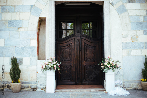 gate of a Romanesque church with flower vases on the sides ... Flower Vases For Church on bridesmaid bouquets for vases, church sanctuary flowers, plants for vases, church flowers large, church flower decorations, church flowers for christmas, church wedding flowers, church pew decorations for weddings, flower arrangements for vases, jelly beads for vases,