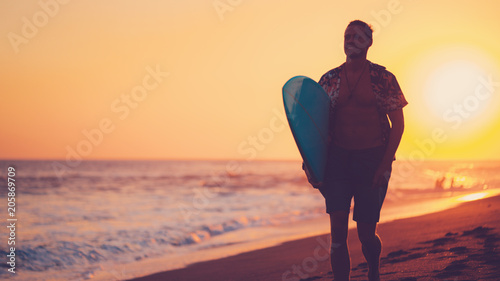 Fototapety, obrazy: Silhouette of man surfer walking on the beach near the ocean with short surfboard at sunset